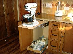 A CONVENIENT MIXER STAND HIDES IN THE CABINET WITH DRAWER SPACE FOR BLADES  AND PADDLES.